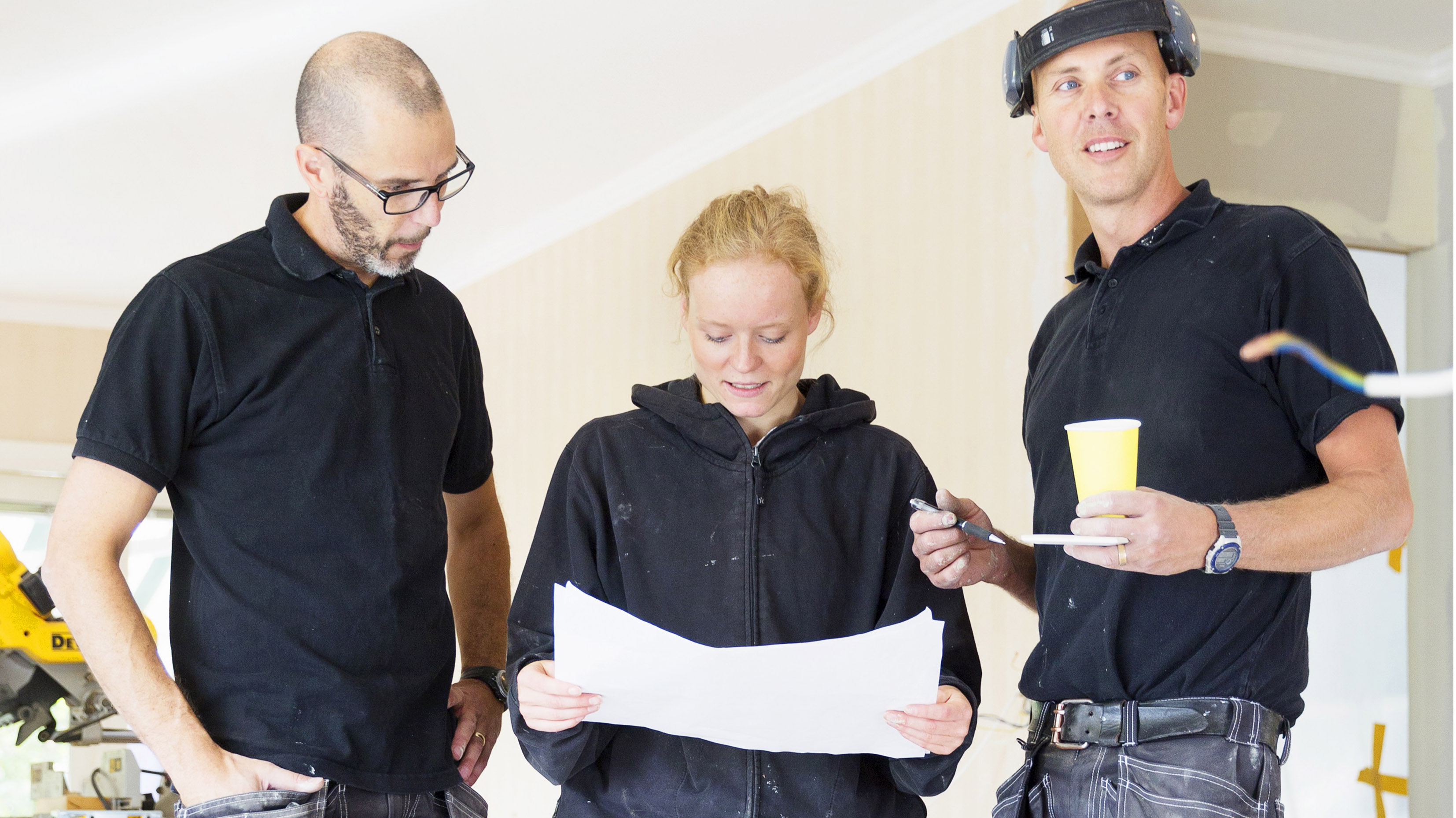 Tre hantverkare tittar på en skiss